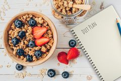 Homemade granola and fresh berries on wood table with note book and text diet plan concept, copy space.  royalty free stock image