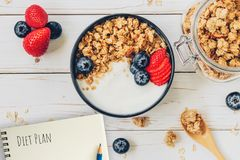Homemade granola and fresh berries on wood table with note book and text diet plan concept, copy space.  royalty free stock photography