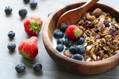 Homemade granola with fresh berry in wooden bowl stock photo