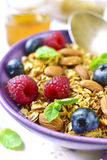 Homemade granola with fresh berry for a breakfast in a purple bo Stock Photos