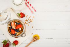 Homemade granola in a glass jar on a white table. Healthy food. Homemade granola in a glass jar on a white table. Healthy food Stock Photo