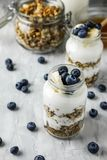 Homemade granola in a glass jar with yogurt and blueberries on a gray concrete background with a bottle of milk and. Honey. Food photography of a healthy Stock Images