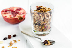 Homemade granola in a glass with pomegranate on white table Stock Photo