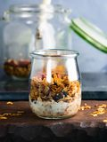 Homemade granola with honey and chestnuts. Homemade granola with honey, raisins, cherries, sesame and chestnuts in a glass on wooden board stock photos