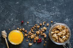 Homemade granola in jar and honey on dark background. Homemade granola in jar and honey on dark slate background. Top view, copy space for text Royalty Free Stock Image