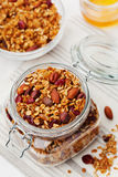 Homemade granola in jar on white table, healthy breakfast of oatmeal muesli, nuts, seeds and dried fruit. Homemade granola in jar on table, healthy breakfast of Stock Photography