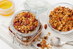 Homemade granola in jar on white table, healthy breakfast of oatmeal muesli, nuts, seeds and dried fruit. Homemade granola in jar on table, healthy breakfast of Royalty Free Stock Photo