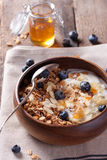 Homemade granola with nuts, candied oranges, fresh blueberries, yogurt and honey Stock Photo