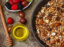 Homemade granola with nuts, honey and fresh berries - raspberries, strawberries, mulberries, gooseberries. Healthy Breakfast. Homemade granola with nuts, honey Royalty Free Stock Image