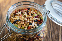 Homemade granola in open glass jar. On rustic wooden background royalty free stock photography