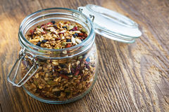 Homemade granola in open glass jar. On rustic wooden background royalty free stock image