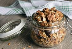 Homemade granola in open glass jar on rustic wooden background stock images