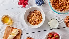 Plate with granola, berries, milk, honey on a white wooden table. Top view Stock Images