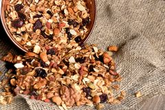 Homemade granola spilling from bowl on wooden table.  Stock Photos
