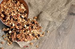 Homemade granola spilling from bowl on wooden table.  Royalty Free Stock Image