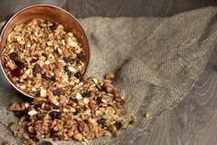 Homemade granola spilling from bowl on wooden table.  Stock Image