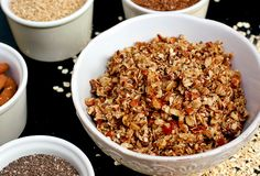 Homemade granola in white bowl with almond and seeds on black background stock photo