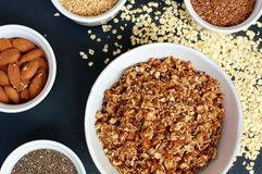 Homemade granola in white bowl with almond and seeds on black background royalty free stock images