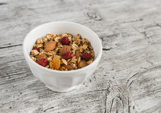 Homemade granola in white bowl on bright wooden surface. Healthy food Stock Photos