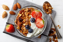 Homemade granola with yogurt and berries. Bowl of homemade granola with yogurt and fresh berries from top view stock photos