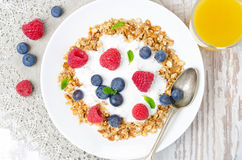 Homemade granola with yogurt, fresh berries and a glass of juice Stock Images