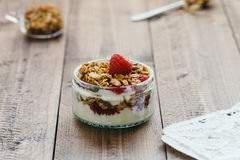 Homemade Granola and Yogurt with Fresh Raspberries on Rustic Table. Horizontal food scene of small glass ramekin layered with granola, natural yogurt and fresh Stock Images