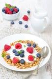 Homemade granola with yogurt, raspberries, blueberries, vertical Stock Image