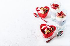 Homemade granola with yogurt in red heart plate on white table. Romantic breakfast. Free space for your text. stock photos
