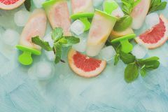 Homemade grapefruit popsicles with grapefruit slices on a mint wooden background. Top view. Copy space. Flat lay. Toned stock images