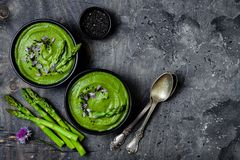 Homemade green spring asparagus cream soup decorated with black sesame seeds and edible chives flowers. stock images