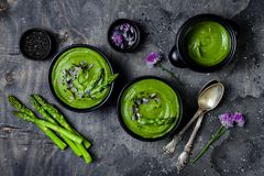 Homemade green spring asparagus cream soup decorated with black sesame seeds and edible chives flowers. Homemade green spring asparagus cream soup decorated royalty free stock image