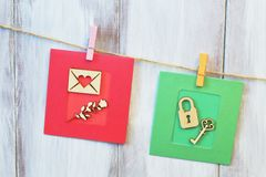 Composition of greeting cards hanging on jute cord. Vintage letter and rose on red paper background, lock and key on green stock photography