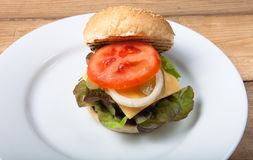 Homemade grilled hamburger on white plate on wooden table Royalty Free Stock Photos