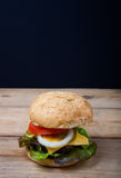 Homemade grilled hamburger on wooden table with black background Stock Photography