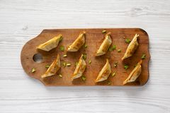 Homemade gyoza on a rustic wooden board over white wooden surface, top view. Flat lay, overhead, from above. Closeup.  royalty free stock images