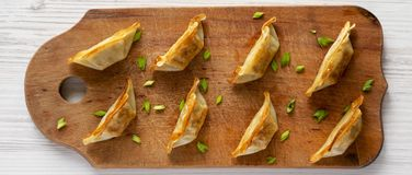 Homemade gyoza on a rustic wooden board on a white wooden surface, top view. Flat lay, overhead, from above. Closeup.  royalty free stock images