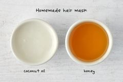 Homemade hair mask made out of coconut oil and honey. Wooden background royalty free stock images