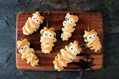 Halloween mummy jalapeno poppers on wooden server. Homemade Halloween mummy jalapeno poppers, top view on wooden server with spiders royalty free stock images