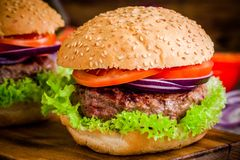 Homemade hamburger with fresh green lettuce, tomato and red onion closeup Royalty Free Stock Photography