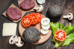 Homemade hamburger ingredients. Raw minced beef, fresh black bun, slice of cheese, tomato, onion rings, lettuce on wood. Background Stock Images