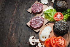 Homemade hamburger ingredients. Raw minced beef, fresh black bun, slice of cheese, tomato, onion rings, lettuce on wood Royalty Free Stock Photos