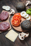 Homemade hamburger ingredients. Raw minced beef, fresh black bun, slice of cheese, tomato, onion rings, lettuce on wood background.  Royalty Free Stock Photo