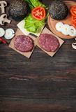 Homemade hamburger ingredients. Raw minced beef, fresh black bun, slice of cheese, tomato, onion rings, lettuce on wood background.  Stock Photography
