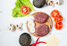Homemade hamburger ingredients. Raw minced beef, fresh black bun, slice of cheese, tomato, onion rings, lettuce on wood white back. Ground Stock Photos