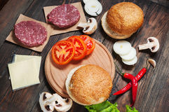 Homemade hamburger ingredients. Raw minced beef, fresh bun, slice of cheese, tomato, onion rings, lettuce on wood Stock Image