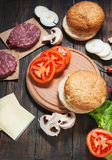 Homemade hamburger ingredients. Raw minced beef, fresh bun, slice of cheese, tomato, onion rings, lettuce on wood background Royalty Free Stock Images