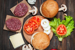 Homemade hamburger ingredients. Raw minced beef, fresh bun, slice of cheese, tomato, onion rings, lettuce on wood background.  Royalty Free Stock Photos