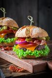 Homemade hamburger with onion, tomato and lettuce. On wooden plank Royalty Free Stock Images