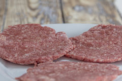Homemade hamburger patties. Three homemade hamburger patties on a plate on a rustic wooden table Stock Photography