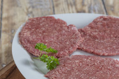 Homemade hamburger patties. Three homemade hamburger patties on a plate on a rustic wooden table Royalty Free Stock Image